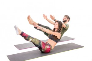 Fit people doing crunches on fitness mats - isolated on white.